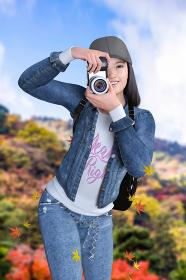 木が紅く紅葉した山を背景にカメラを構えた帽子をかぶった笑顔の女の子