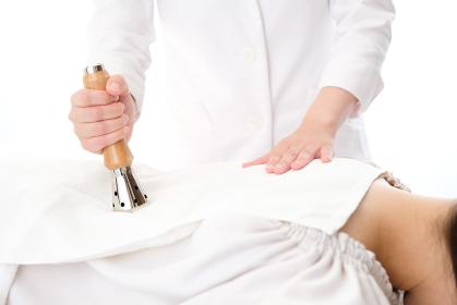明るい室内で女性の背中をMT式温灸器で施術する鍼灸師