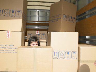 Girl hiding in boxes in moving van