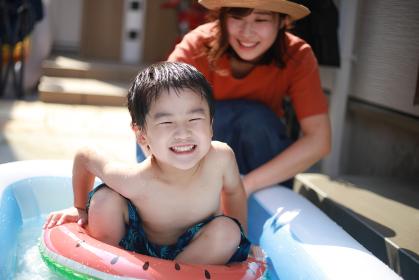 ビニールプールで遊ぶ親子