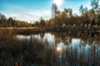 Sun in colorful mood on a lake with reflections on the water