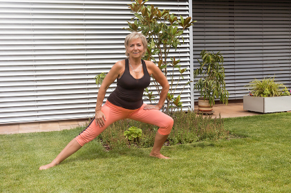 Attractive senior blond woman doing her stretches in the garden