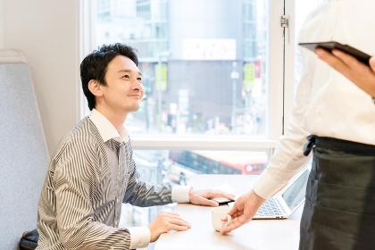 カフェで仕事中に注文したコーヒーを受け取る男性