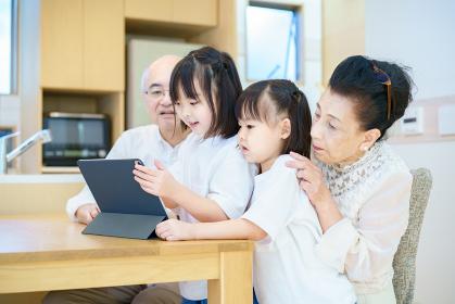 タブレットPCを操作するシニア夫婦と孫たち
