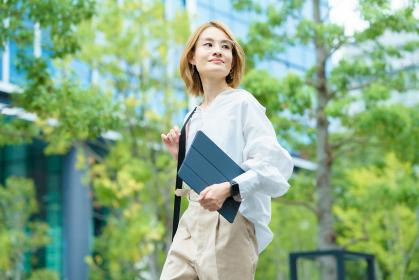 緑あふれるオフィス街を歩く女性