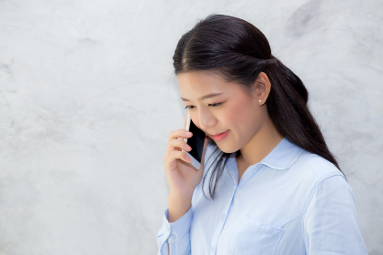 Beautiful young asian woman talking mobile phone and smile stand