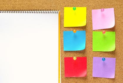 コルクボードにピンで留めた6枚の色紙のメモ紙とスケッチブックの白い画用紙