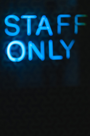 Blurred neon letters, signboard staff only on a black wall close-up.