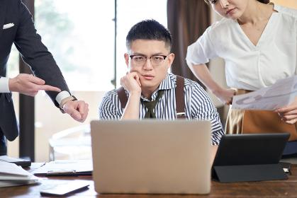 仕事量と締切に追われるアジア人男性ビジネスマン