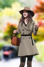 町中の紅葉した自然を背景にポーズを取るコートを着た女性