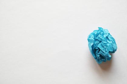 灰色の紙の右側に置いた青色の紙礫とコピースペース