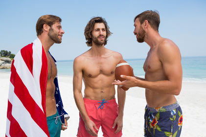 Shirtless male friends talking while standing at beach