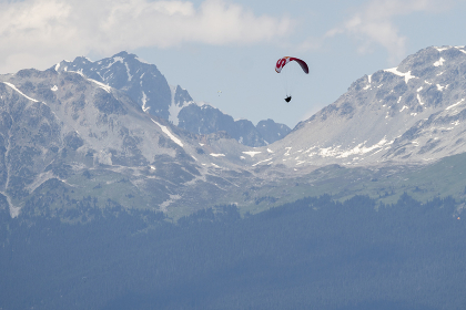 Paragliders fly high above snow covered mountains on a sunny day.