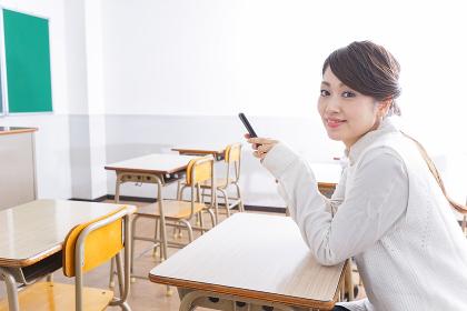 教室で携帯電話を使う学生