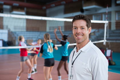 Smiling coach standing in the volleyball court