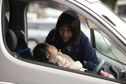 眠る子供をチャイルドシートに乗せる母親