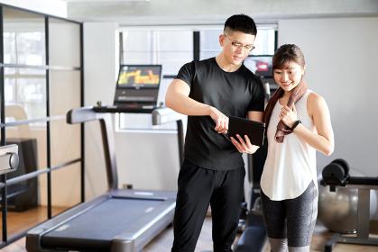 タブレットを使って指導するアジア人男性パーソナルトレーナー