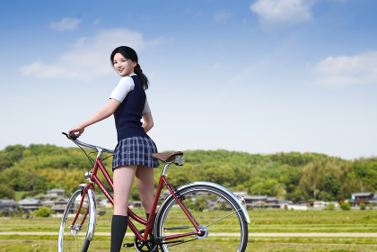午前中の授業だけの土曜日の下校途中の女子高生が籠のないシティサイクルに乗りのどかな道を進む