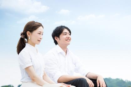 青空が綺麗な屋外で座って会話するカップル