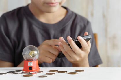 クレジットカードでスマホゲームに課金しようとする小学生の男の子