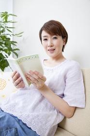 母子手帳を開いて微笑む妊婦
