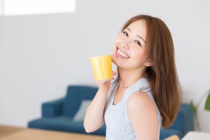 部屋で飲み物を飲む女性