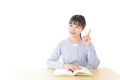勉強をしながら指を指す若い女子学生