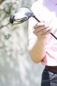 ゴルフクラブを持って微笑むシニア男性