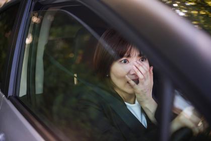 運転中に驚いた表情をする女性