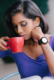 Young Indian woman having coffee and reading book