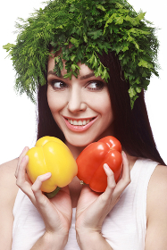 A young girl with a smile. Diet, weight loss. Keeps vegetables, at the head of the greens.