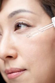 顔に美容液を垂らす中年の日本人女性