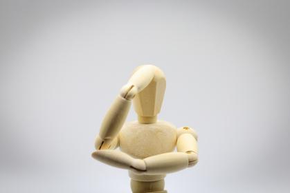 頭を抱えるデッサン人形のイメージ