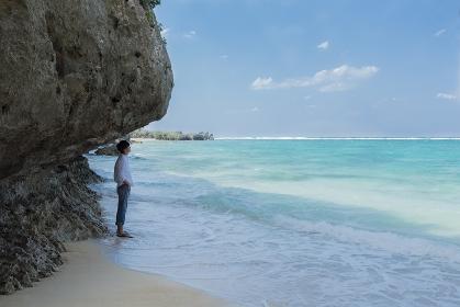海岸で海を見ている日本人男性