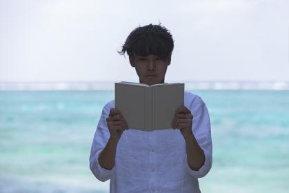 海辺で本を読む日本人男性
