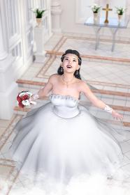 チャペルの祭壇の前で笑顔で上を見上げる純白のウエディングドレスを着た幸せそうな花嫁