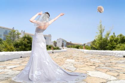 晴天の空に向かってブーケトスをする純白のウエディングドレスを着た花嫁