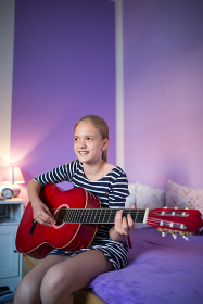Teenage girl playing a  guitar in her lovely room
