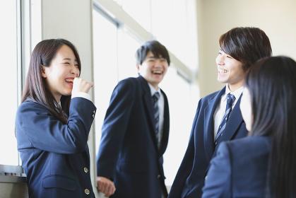廊下で会話している高校生たち