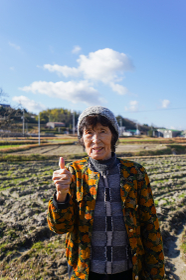 田舎でグッドサインをする高齢の女性