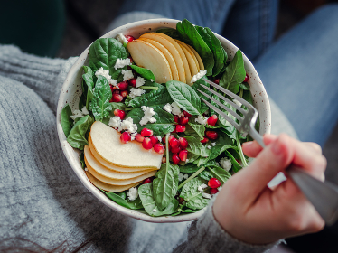 Girl holding salad with spinach, pear, pomegranate, cheese