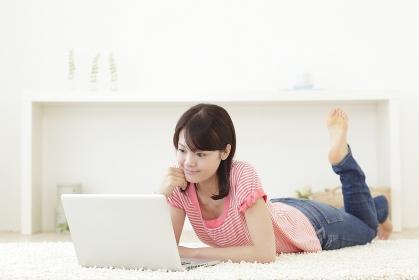 リビングで寝そべりパソコンをする若い女性