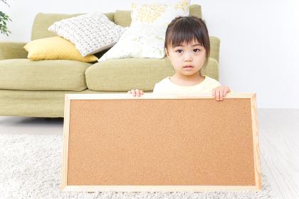 泣きながらボードを持つ子供