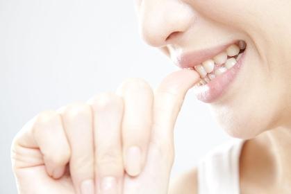 爪を噛む女性の手元