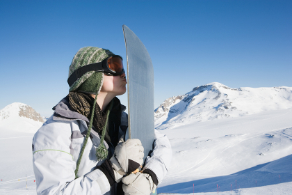Snowboarder kissing snowboard