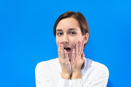 驚いた表情の若い女性(カラフルな色の背景)