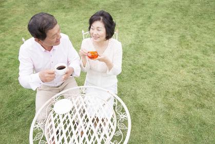 庭でお茶をするシニア夫婦