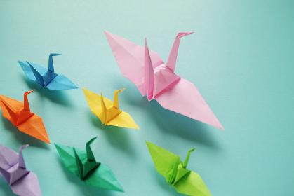 複数の色とりどりの小さな折り鶴を率いているピンクの大きな折り鶴。