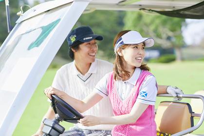 ゴルフカートに乗る日本人カップル