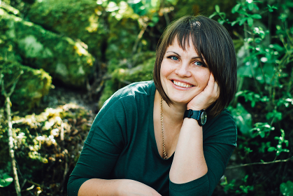 smiling young brunette woman in a green garden